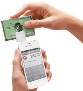 Hands running credit card through Square device on smartphone
