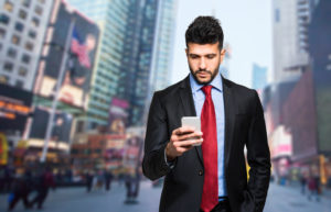 Businessman holding mobile smartphone using app texting sms message