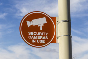 Orange Security Camera In Use Sign on Gray Post and Partly Sunny Background II