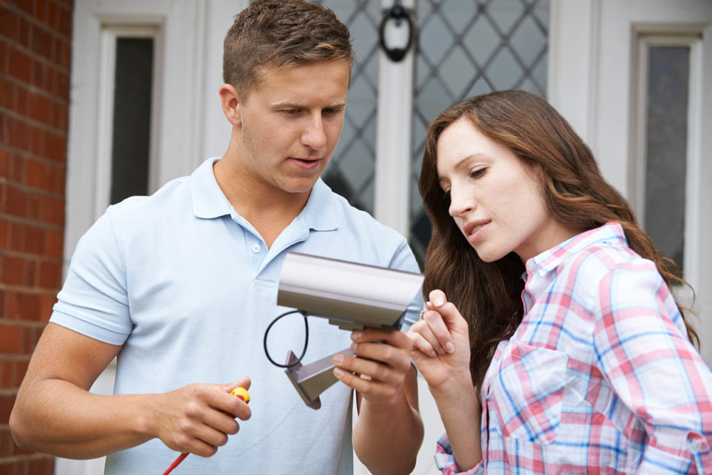 man and woman inspecting a new security camera