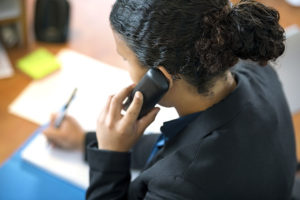 Receptionist Using Phone In Office